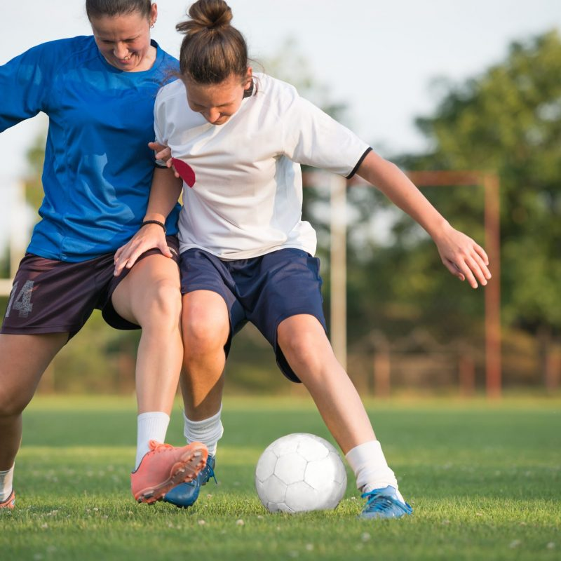 stock-photo-two-female-soccer-players-on-field-147820472